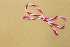 String tied in a bow, over brown paper Stock Image