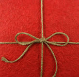 String tied in a bow on red paper Royalty Free Stock Images