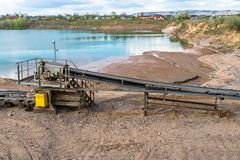 A string of transport belting in a gravel pit for transporting gravel and sand over long distances, belts go along the lake. A string of transport belting in a stock image