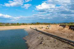 A string of transport belting in a gravel pit for transporting gravel and sand over long distances, belts go along the lake. A string of transport belting in a royalty free stock image