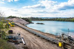 A string of transport belting in a gravel pit for transporting gravel and sand over long distances, belts go along the lake. A string of transport belting in a royalty free stock photography