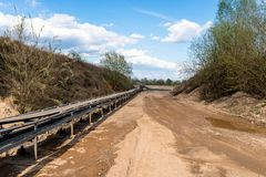 A string of transport belting in a gravel pit for transporting gravel and sand over long distances, belts go along the road. A string of transport belting in a stock photo