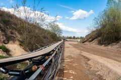 A string of transport belting in a gravel pit for transporting gravel and sand over long distances, belts go along the road. A string of transport belting in a royalty free stock photo