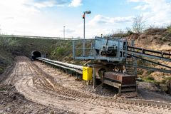 A string of transport belting in a  gravel pit for transporting gravel and sand over long distances, the belts go under of the roa. D royalty free stock images