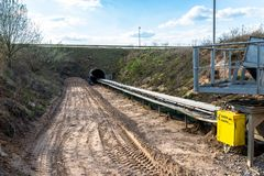 A string of transport belting in a  gravel pit for transporting gravel and sand over long distances, the belts go under of the roa. D royalty free stock image