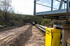 A string of transport belting in a  gravel pit for transporting gravel and sand over long distances, the belts go under of the roa. D royalty free stock photo
