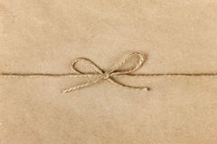 String or twine tied in a bow on kraft paper Stock Photos