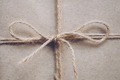String or twine tied in a bow on kraft paper texture stock photography