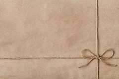 String or twine tied in a bow on kraft paper Stock Image