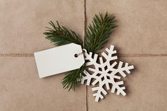 String or twine tied in a bow with tag, fir tree and wooden snowflake on kraft paper Stock Photos