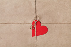 String or twine tied in a bow with tag in shape of heart on kraft paper Stock Photos