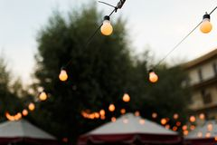 Warm light bulbs at the evening event. String wired with warming Light Bulbs hanging in the area of wedding events celebration in the night royalty free stock photos