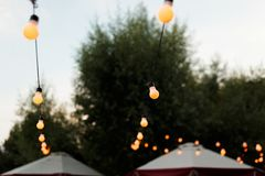 Warm light bulbs at the evening event. String wired with warming Light Bulbs hanging in the area of wedding events celebration in the night royalty free stock photography