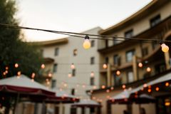 Warm light bulbs at the evening event. String wired with warming Light Bulbs hanging in the area of wedding events celebration in the night stock photos