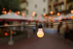 Warm light bulbs at the evening event. String wired with warming Light Bulbs hanging in the area of wedding events celebration in the night stock photography