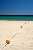 String of yellow buoys on sunny, sandy beach Royalty Free Stock Photo