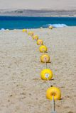 String of yellow marker buoys on sandy beach Royalty Free Stock Photos