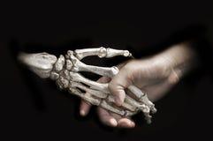 Stringa la mano con l'osso di morte sul contratto nero di accordo di manifestazione fotografia stock