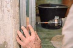 Stringa le viti Avviti le viti con lo strumento Riparazione nell'appartamento Installazione della porta Lavoro del fabbro fotografia stock libera da diritti
