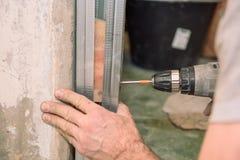 Stringa le viti Avviti le viti con lo strumento Riparazione nell'appartamento Installazione della porta Lavoro del fabbro fotografia stock