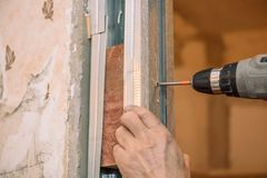 Stringa le viti Avviti le viti con lo strumento Riparazione nell'appartamento Installazione della porta Lavoro del fabbro immagine stock libera da diritti