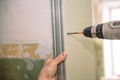 Stringa le viti Avviti le viti con lo strumento Riparazione nell'appartamento Installazione della porta Lavoro del fabbro fotografie stock libere da diritti