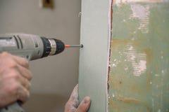 Stringa le viti Avviti le viti con lo strumento Riparazione nell'appartamento Installazione della porta Lavoro del fabbro immagini stock libere da diritti