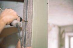 Stringa le viti Avviti le viti con lo strumento Riparazione nell'appartamento Installazione della porta Lavoro del fabbro immagini stock