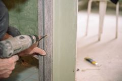 Stringa le viti Avviti le viti con lo strumento Riparazione nell'appartamento Installazione della porta Lavoro del fabbro fotografie stock