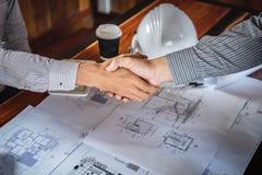 Stringendo le mani di collaborazione, di ingegneria di costruzione o dell'architetto per discutere un modello mentre controllando immagine stock libera da diritti