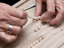 Stringing pearls on a necklace Royalty Free Stock Photo