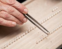 Stringing pearls on a necklace Stock Photo