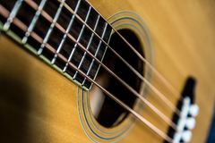 Strings of acoustic guitar. Close up of strings on wooden acoustic guitar body stock image