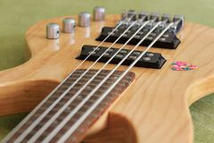 5 strings bass guitar and a pick. A closeup with a 5 strings electric bass guitar and a pick royalty free stock photo