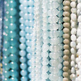 Strings of beads or necklaces. Strings of white, tan and blue beads hanging down Royalty Free Stock Photography