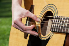 Strings. A close up of guitar strings and a hand Stock Image