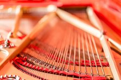 Strings close-up. Vintage red classical grand piano. Musical instrument abstract. Strings close-up. Vintage red classical grand piano. Musical instrument Royalty Free Stock Images
