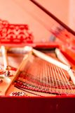 Strings close-up. Vintage red classical grand piano. Musical instrument abstract. royalty free stock photos