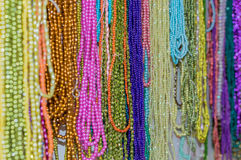 Strings of colorful beads hung at outdoor crafts market Stock Images