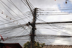 Strings of Electricity Cables Connected to Wooden Pole Stock Photography