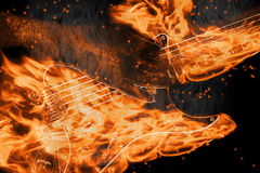 Strings of fire. Playing a burning string guitar with flames and smoke Stock Photos