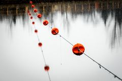 Strings of floats on a safety cable. String of floats on a safety cable before the dam at Healey Falls in Campbellford, Ontario, Canada Royalty Free Stock Image