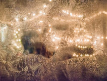 Strings of light through an icy window. Lights and ice make a great texture and background Stock Photos