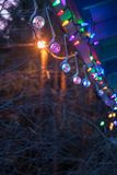 Strings ofcolorful christmas lights hanging from a roof. Christmas lights on a string hang outside in the evening with copy space royalty free stock photography
