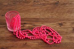 Strings of pink beads displayed in a fancy glass vase Stock Photography