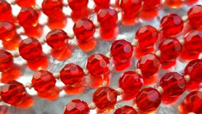 Strings of red glass beads on bright background. royalty free stock photography