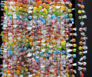 Strings of sugar candy beads, background. Sugar candy beads in transparent film tied together with golden cord; the strings hung for display; background Stock Photos