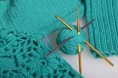 Strings of thread for knitting emerald color and hooks for knitting. Lie on a ready knitted product. Strings of thread for knitting emerald color and hooks for stock photos