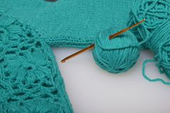 Strings of thread for knitting emerald color and hooks for knitting. Lie on a ready knitted product. Strings of thread for knitting emerald color and hooks for royalty free stock photography