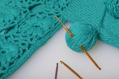 Strings of thread for knitting emerald color and hooks for knitting. Lie on a ready knitted product. Strings of thread for knitting emerald color and hooks for stock photography
